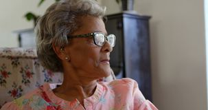 Front view of Caucasian senior woman relaxing at nursing home 4k. Front view of Caucasian senior woman relaxing at nursing home. She is looking away 4k stock video footage