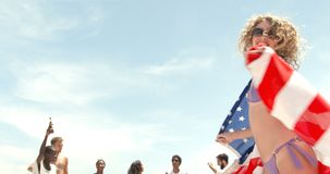 Front view of Caucasian woman dancing with American flag on the beach 4k stock footage