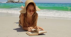 Front view of Caucasian woman in hat reading book on the beach 4k stock video footage