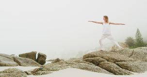 Front view of Caucasian woman performing yoga on the beach 4k. Front view of Caucasian woman performing yoga on the beach. She is stretching her arms 4k stock video footage