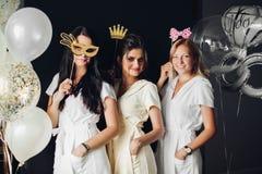 Bridesmaid wearing funny masks posing with braid