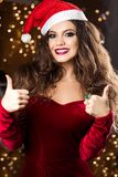 Front view of cheerful woman in santa hat showing sign okay. Front view of cheerful woman wearing red dress and santa hat, looking at camera and showing sign stock photo