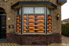 Front view of a cheese store window with round yellow cheese stickers, brown brick building. royalty free stock photo