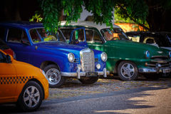 Front view of  classic retro vintage cars standing in dark shadows under the trees Royalty Free Stock Image