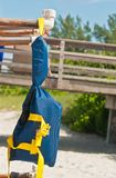 Child`s life vest at a tropical beach. Front view, close distance of a child`s life vest hanging on wood rack, for the protection of children swimming at a stock photo