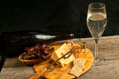 Food pairings for a french wine tasting event. Front view, close distance of food pairings, of cheese, cheese knife, crackers, cork and metal cap, on wood plate royalty free stock photography