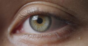 Blinking green eye. Front view close up detail of the green eye of a woman looking ahead and blinking stock footage