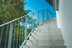 Front view close up of empty white concrete staircase and metal railing at outside buildings with blue sky background. Royalty Free Stock Photo