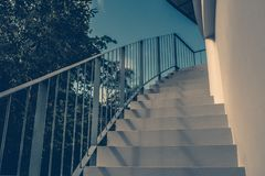 Front view close up of empty white concrete staircase and metal railing at outside buildings with blue sky background. Stock Image