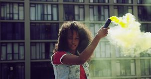 Fashionable young woman on urban rooftop using a smoke grenade stock video footage