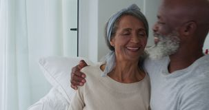 Mature couple at home. Front view close up of a mature mixed race couple embracing and smiling sitting on a sofa at home stock video