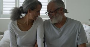 Mature couple at home. Front view close up of a mature mixed race couple sitting on their bed, talking, smiling and leaning their heads together stock video