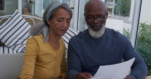 Mature couple at home. Front view close up of a mature mixed race couple using a laptop computer, looking at a document and talking at home stock footage