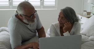 Mature couple at home. Front view close up of a mature mixed race couple using a laptop computer in their bedroom at home stock video footage