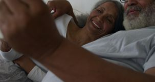 Mature couple at home. Front view close up of a mature mixed race couple using a tablet computer lying in bed at home stock footage