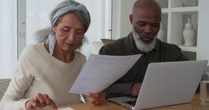 Mature couple at home. Front view close up of a mature mixed race man using a laptop computer and a mature mixed race woman holding a document and discussing stock video
