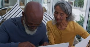Mature couple at home. Front view close up of a mature mixed race man using a laptop computer and a mature mixed race woman holding a document and discussing at stock video footage