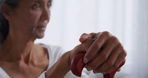 Mature woman at home. Front view close up of a mature mixed race woman holding a walking stick sitting on the sofa at home stock video footage