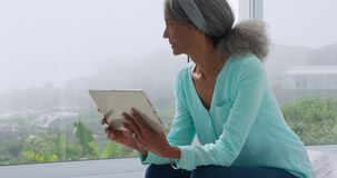 Mature woman at home. Front view close up of a mature mixed race woman using a tablet at home and looking out of the window stock video