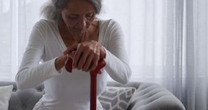 Mature woman at home. Front view close up of a mature mixed race woman using a walking stick and sitting on the sofa at home stock video