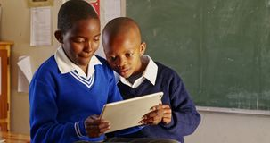 Schoolboys using a tablet during a break at a township school 4k stock video