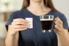 Woman hands holding a coffee cup and saccharin. Front view close up of a woman hands holding a coffee cup and saccharin at home Stock Photo