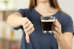 Woman hands holding a coffee cup with thumbs down. Front view close up of a woman hands holding a coffee cup with thumbs down at home Stock Image