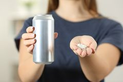 Woman hands holding a soda drink can and saccharin. Front view close up of a woman hands holding a soda drink can and saccharin at home Stock Photo