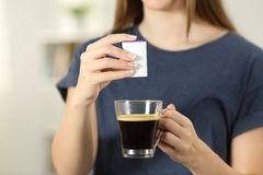 Woman hands throwing saccharin into a coffee cup. Front view close up of a woman hands throwing saccharin into a coffee cup at home Stock Image