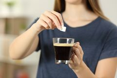Girl hands throwing a sugar cube into a coffee cup. Front view close up of a woman hands throwing a sugar cube into a coffee cup at home Stock Photos