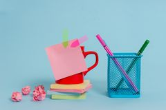 Front view coffee cup colored sticky note arrow banners crushed paper balls stacked pads metal pens holder lying stock photo