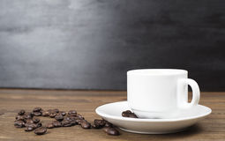 Front view of coffee cup standing on wooden table with coffee beans around on black wall background. Royalty Free Stock Image