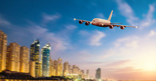 Front view of commercial airplane, blur modern city on background. Concept of travel and transportation. Copyspace for text Stock Images