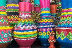 Stack of artistic painted colorful handcrafted pottery vases royalty free stock photo