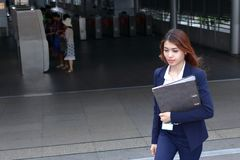 Front view of confident young Asian business woman walking up the stairs at entrance of railway station background. Front view of confident young Asian business Stock Image