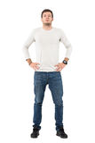 Front view of confident young casual man with arms on hips. Royalty Free Stock Images