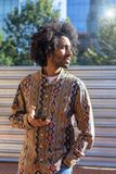Front view of a cool young smiling afro man using a mobile phone while standing outdoors in a sunny day royalty free stock images