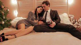 Front view of couple in love laying on the bed and drinking wine for their new year`s anniversary slow motion. Front view of couple in love laying on the bed and stock video