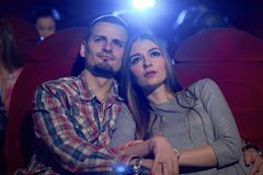 Couple  hugging in cinema. Front view of couple sitting together in cinema, watching comedy or romantic movie. Handsome bearded men hugging beautiful girlfriend stock photos