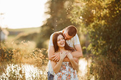 Front view of couple of young boyfriend and girlfriend standing and smiling at camera. Couple embracing and holding by hands each Stock Photography
