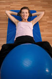 Front View Crunches With a Pilates Ball. A woman exercising with a pilates ball between her legs Stock Photos