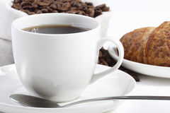 Front view of a cup of hot coffee. With croissants and beans Stock Image