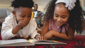 Cute African American sibling lying on floor and reading a storybook. Front view of cute African American sibling lying on floor and reading a storybook in a royalty free stock image