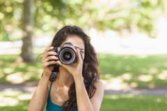 Front view of cute brunette woman taking a picture with her camera Royalty Free Stock Photos