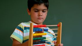 Caucasian boy learning mathematics with abacus against green board in classroom. Front view of cute Caucasian boy learning mathematics with abacus against green stock video footage
