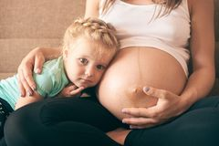 Front view of cute girl sitting on sofa wth pregnant mother stock photography