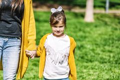 Front view of a cute little girl with a head tie standing in the park and looking at camera while holding hands with mom in a. Front view of a little girl with a stock photo