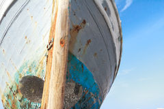 Front view of damaged with time wooden fishing boat on Greek Kos island shore Stock Image