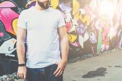 Front View De jonge gebaarde hipstermens gekleed in witte t-shirt is tribunes tegen muur met graffiti Spot omhoog stock foto's