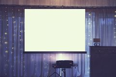 Front view of decorated wedding room with empty white projector screen in the centre. Equipment for video and slideshow projection. At a festive event royalty free stock images